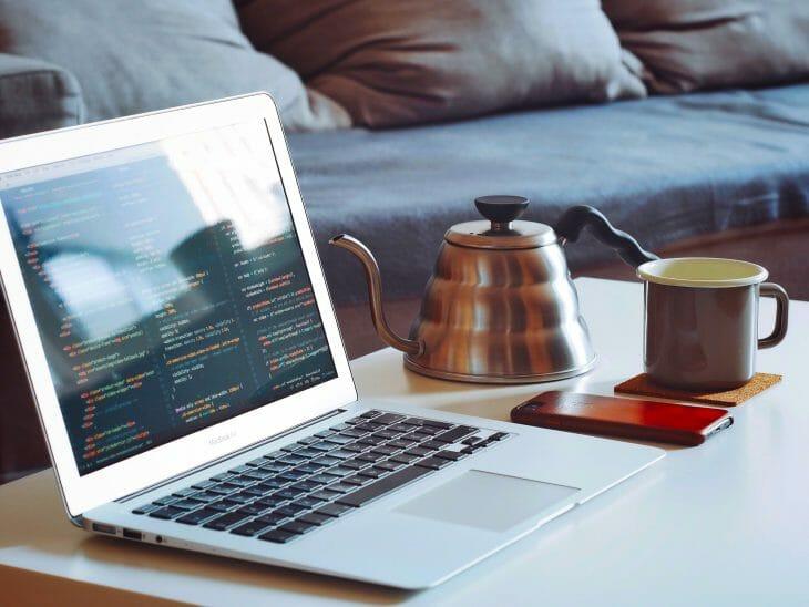 Дизайнерский чайник возле чашки и ноутбука