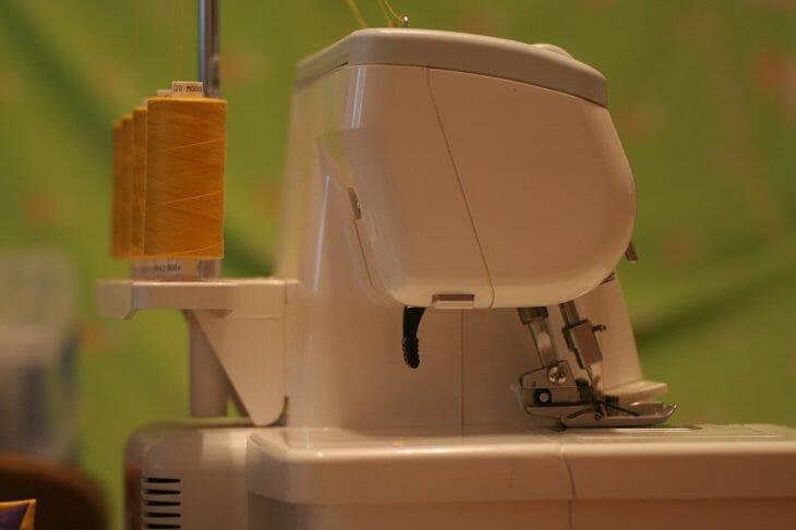 Швейный оверлок возле желтых нитей