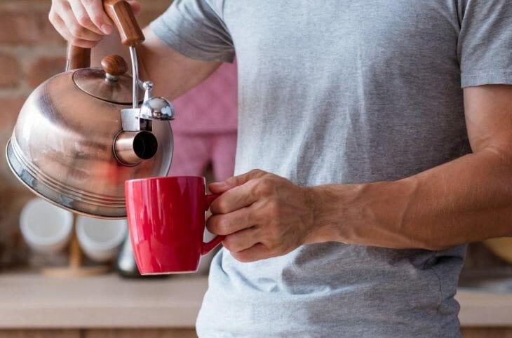 Мужчина наливает кипяток из чайника в чашку