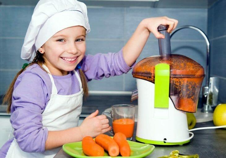 Ребенок выжимает сок из моркови