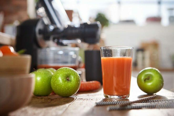 Стакан с яблочным соком на столе