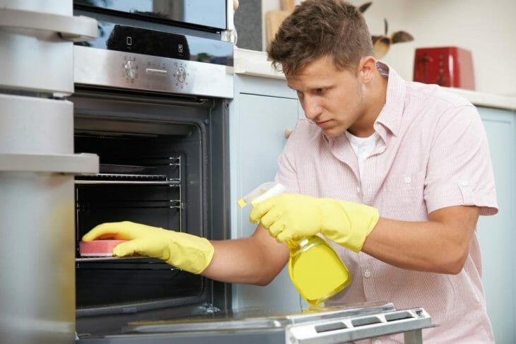 Мужчина моет духовку