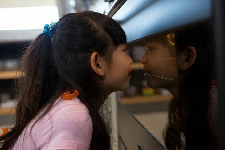 Девочка смотрит на электрическую духовку