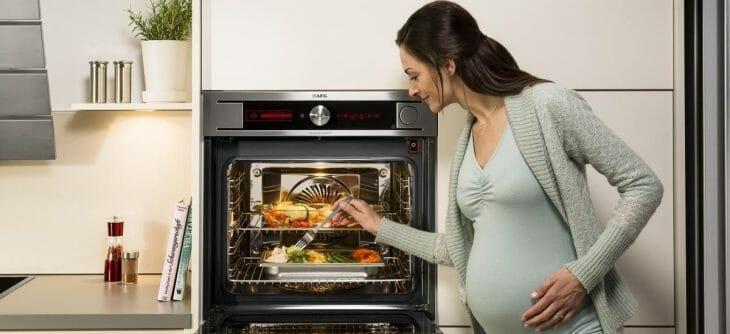 Беременная женщина стоит возле духового шкафа