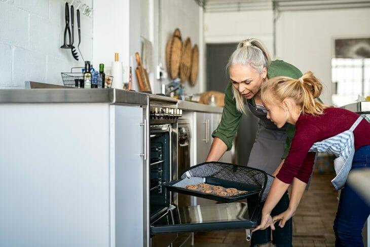 Бабушка и внучка вынимают печенье из духовки
