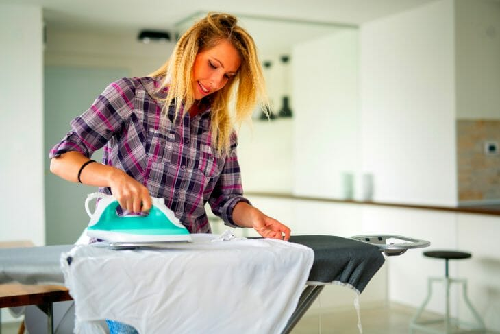 Женщина гладит одежду утюгом