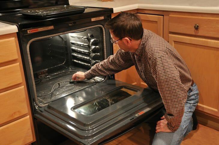 Мужчина осматривает газовую духовку после покупки