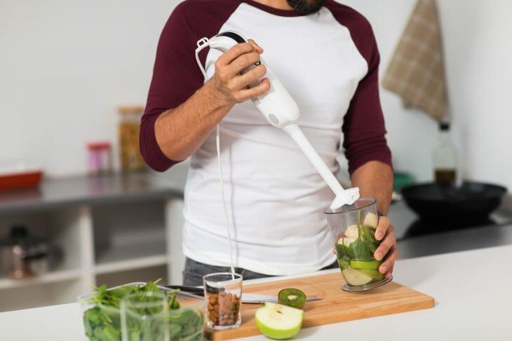 Мужчина использует погружной блендер
