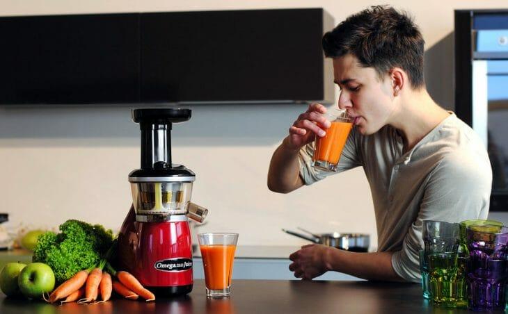 Мужчина пьет свежевыжатый сок
