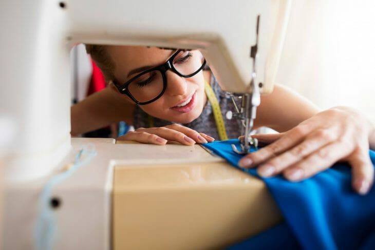 Женщина следит за швов в швейной машине