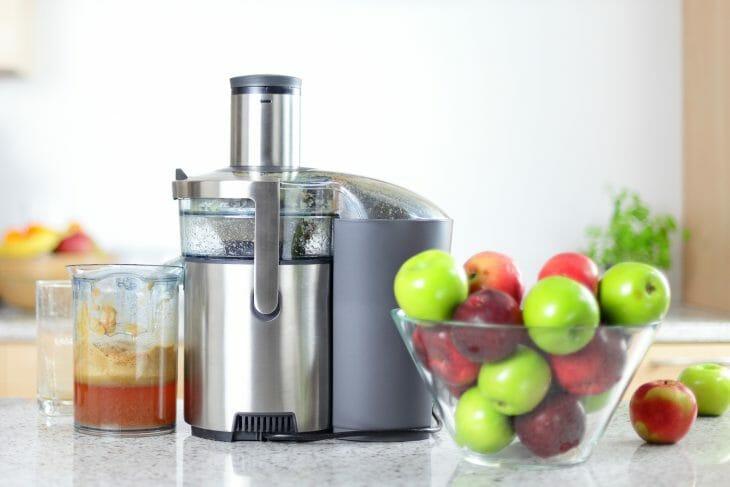 Соковыжималка возле чаши с яблоками