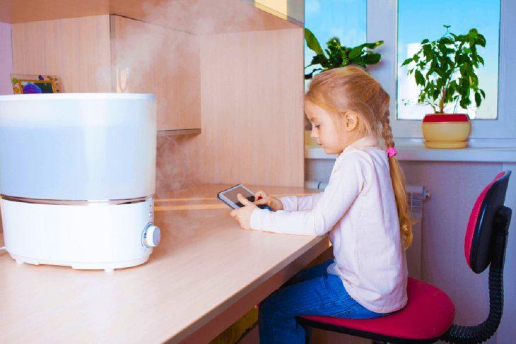 Увлажнитель с ионизатором на столе возле девочки