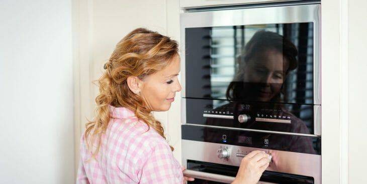 Женщина возле встроенного электрической духовки