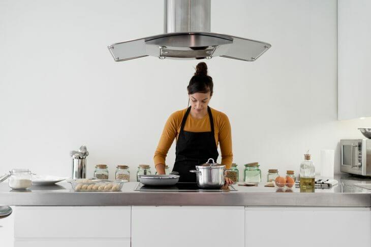 Женщина готовит у плиты