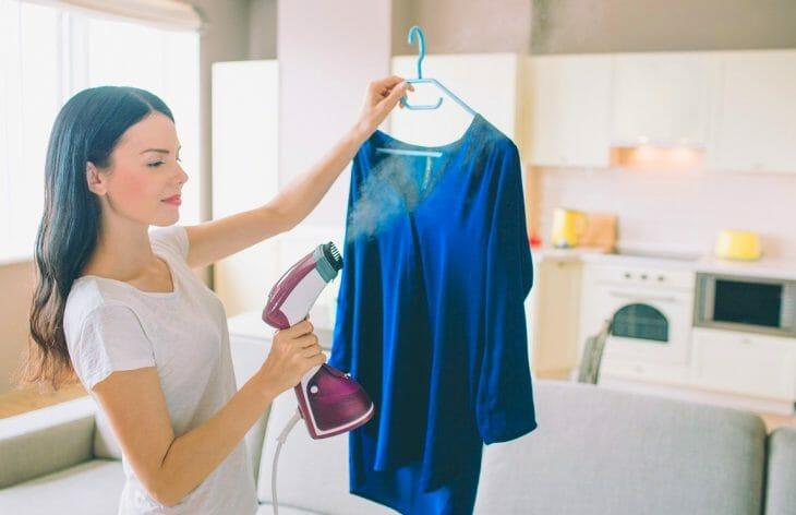 Женщина использует отпариватель с ворсистой щеткой