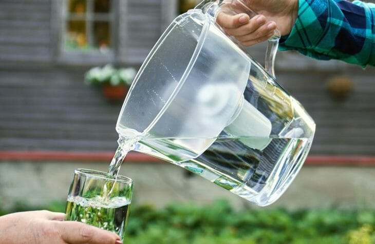 Льют воду в стакан из кувшин фильтра
