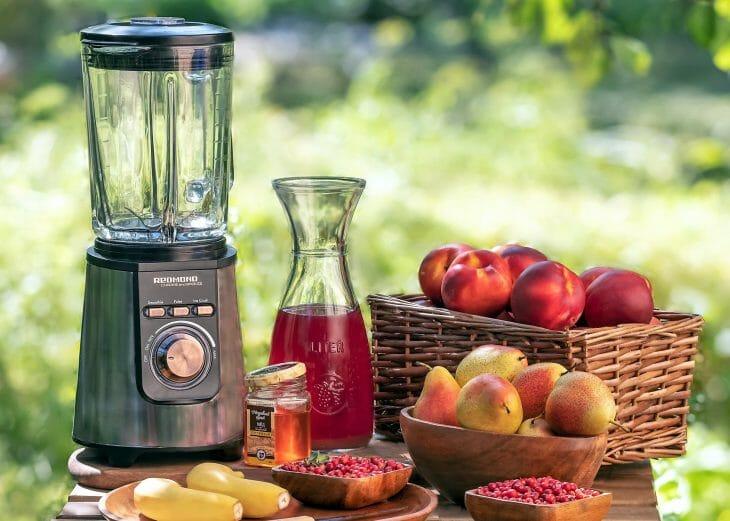 Небольшой блендер со стеклянной чашей возле фруктов на столе