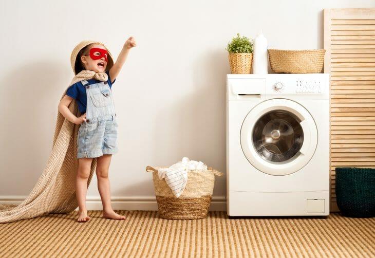 Ребенок играет возле стиральной машины