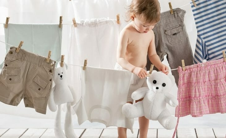 Ребенок возле вещей, который сушатся после стирки