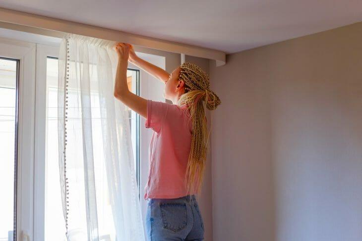 Женщина вешает занавески