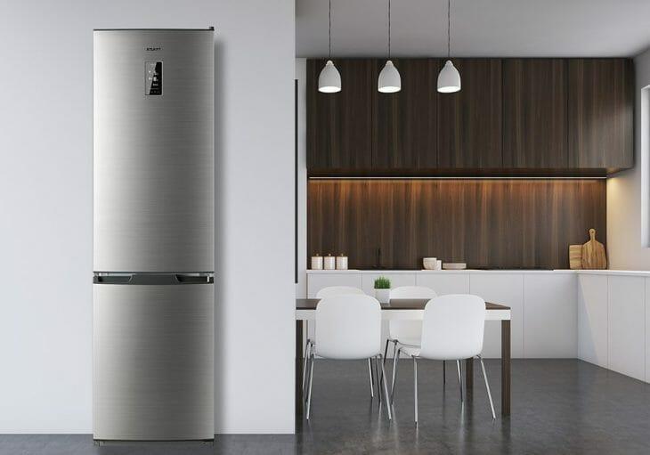 Серый двухкамерный холодильник в интерьере