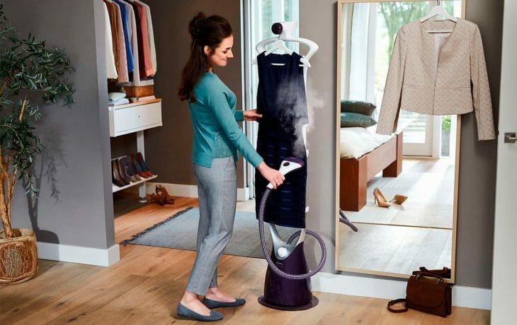 Женщина отпаривает платье на вешалке