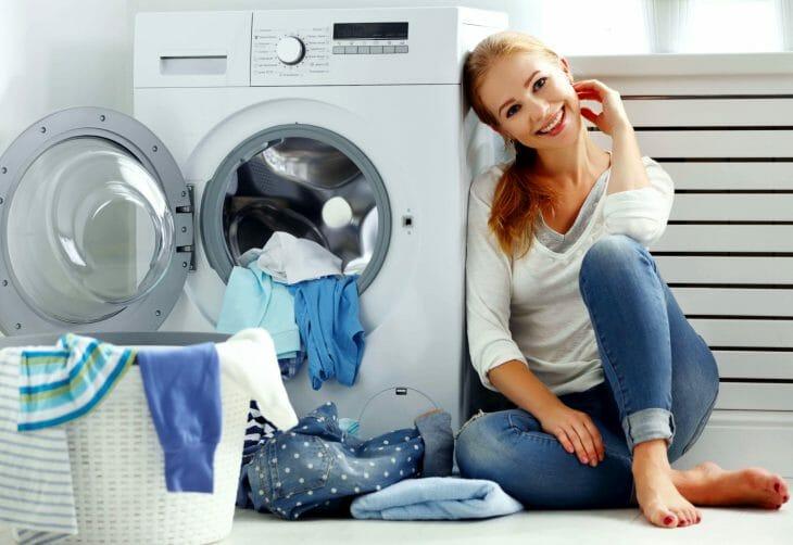Женщина сидит возле компактной стиральной машинки