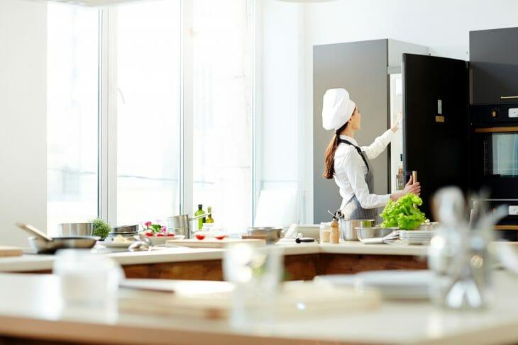 Женщина достает продукты из холодильника