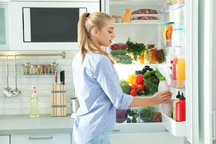 Женщина у раскрытого холодильника