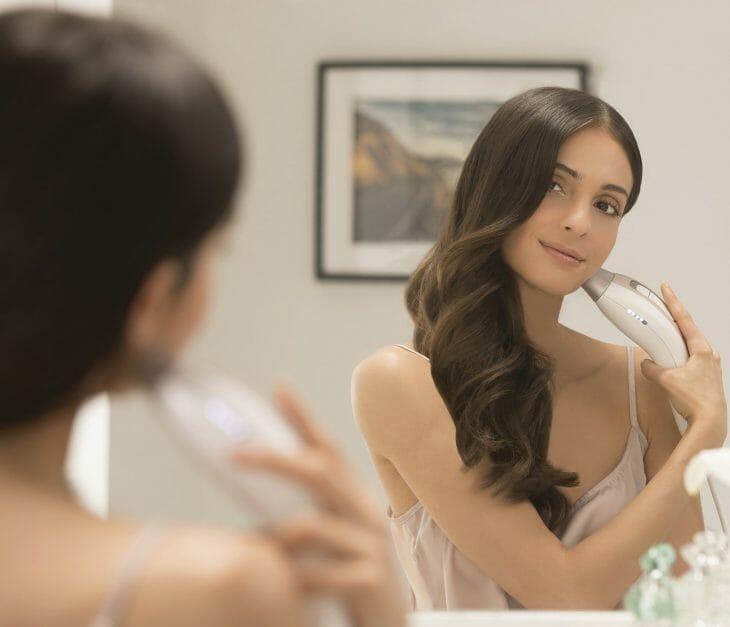 Женщина использует бытовой лазерный эпилятор для лица