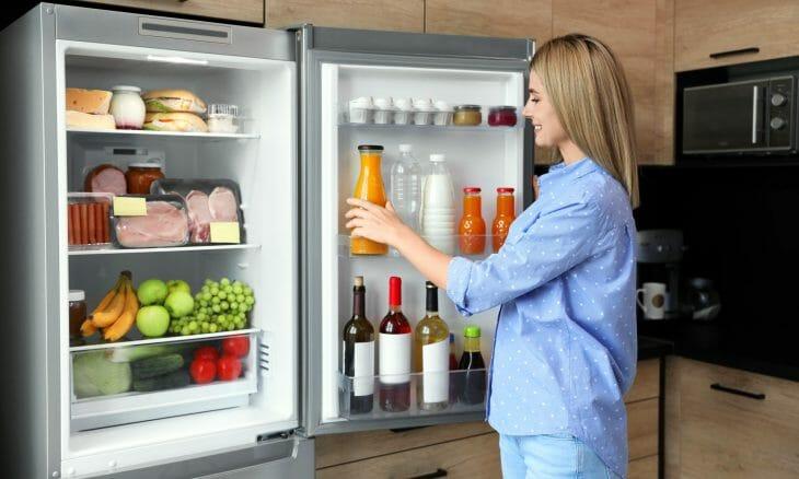 Женщина возле холодильника без морозильной камеры