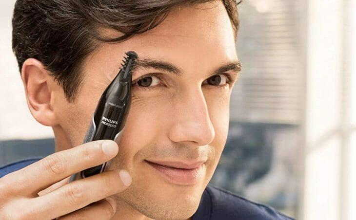 Мужчина использует насадку к триммеру для бровей