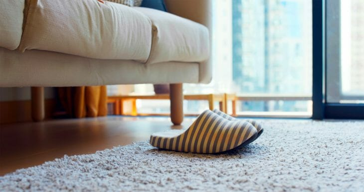 Тапочки на ковре возле дивана