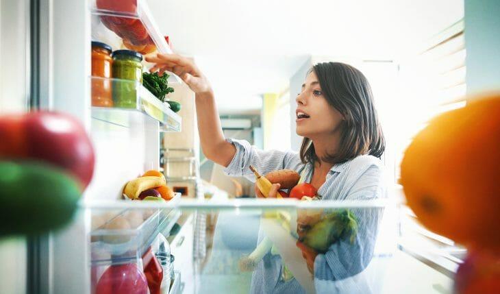 Женщина кладет продукты в холодильник