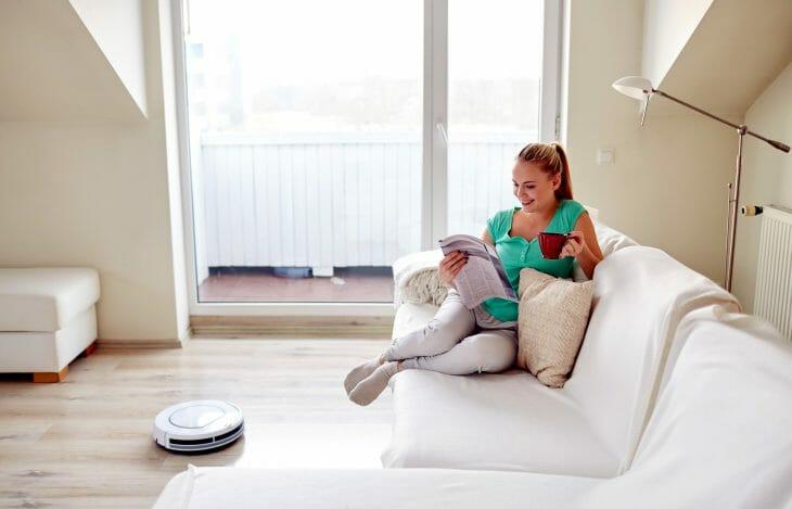 Женщина отдыхает робот пылесос работает