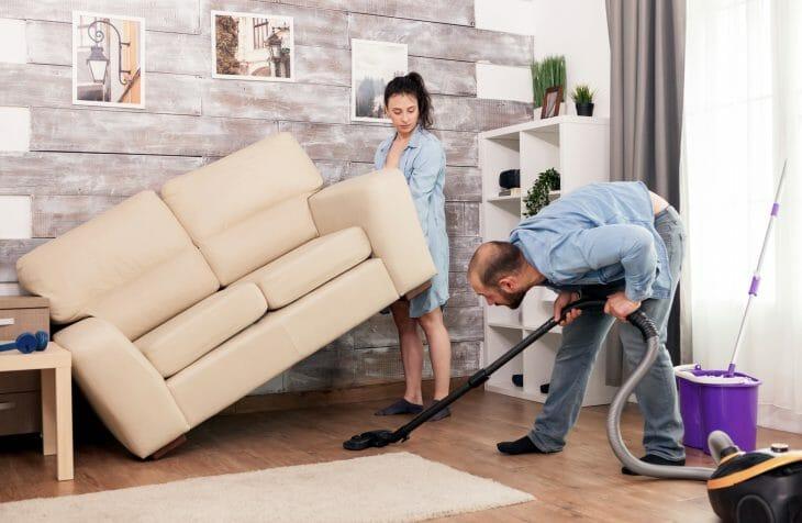 Женщина помогает мужчине пылесосить