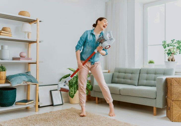Женщина дурачится во время уборки вертикальным пылесосом