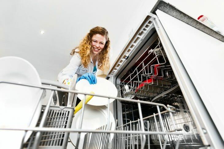 Женщина стоит возле полноразмерной посудомоечной машины
