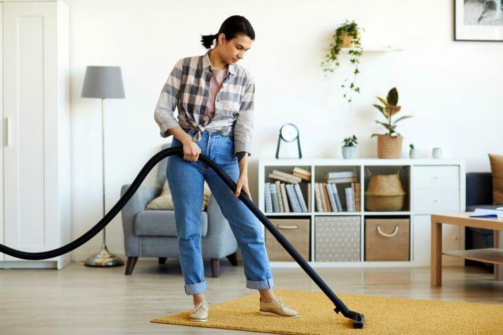 Женщина убирает в комнате пылесосом Томас