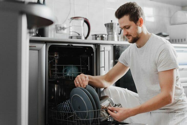 Человек достает посуду с посудомойки