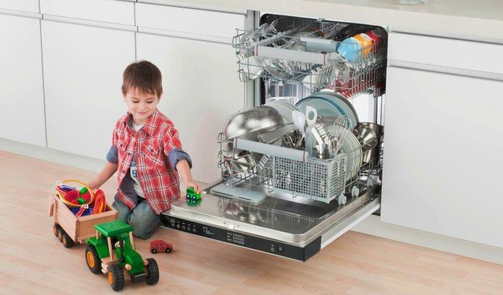 Ребенок играется с машинкой возле посудомойки