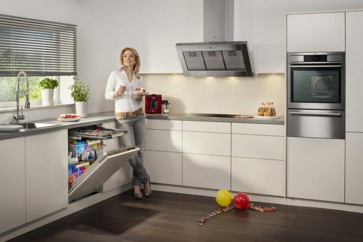Женщина стоит возле посудомойки встроенного типа