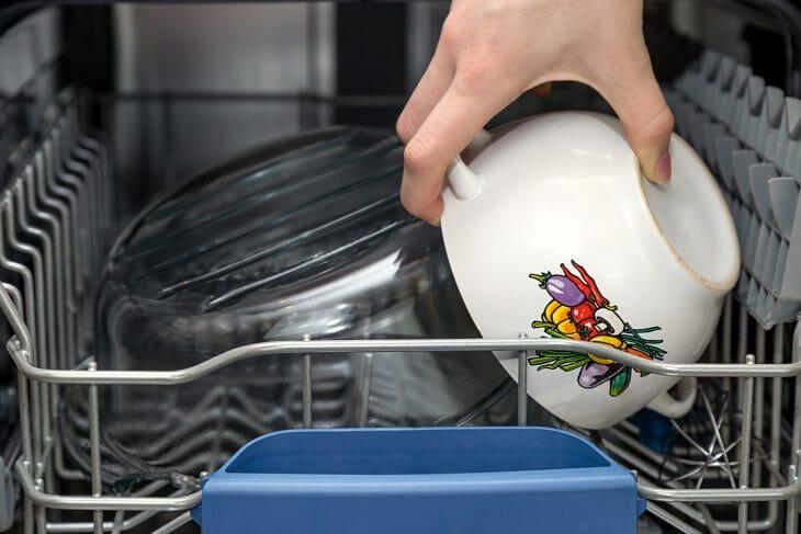 Рука забирает тарелку с посудомойки
