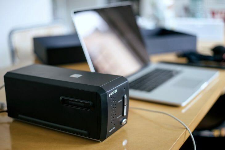 Сканер Plustek для фотопленки возле ноутбука