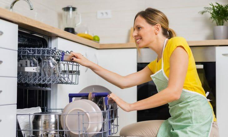 Женщина использует посудомоечную машину