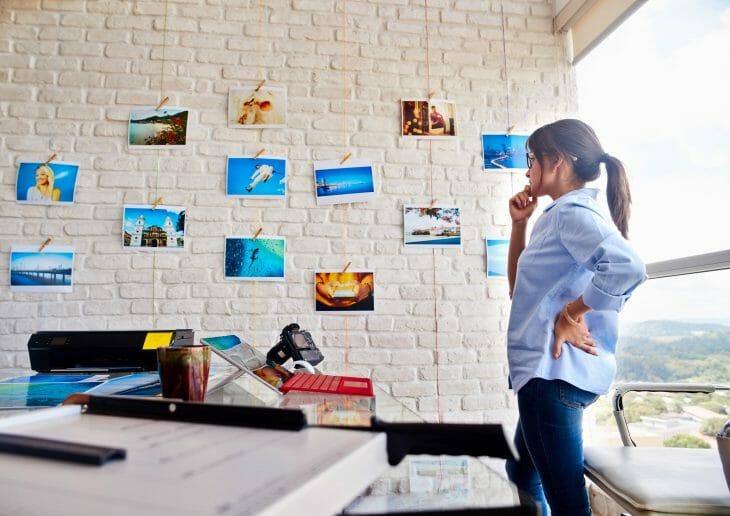 Женщина смотрит на фотографии на стене