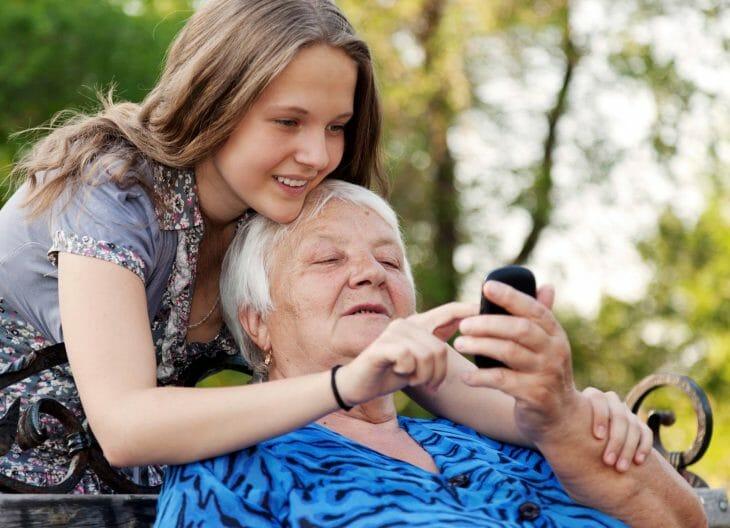 Девочка учит бабушку пользоваться телефоном