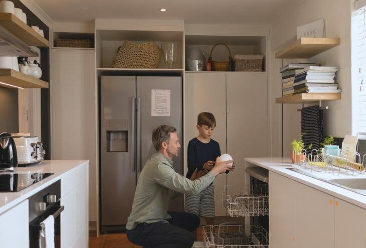 Отец с сыном возле отдельно стоящей посудомоечной машины