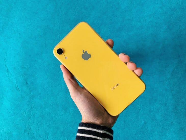 Желтый iPhone Xr в руке