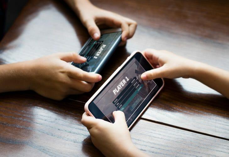 2 детей играет на 2 телефонах